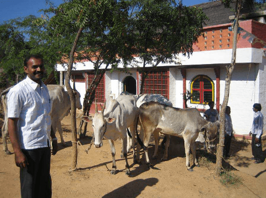 Headmaster Chandra Mohan in front of a building of the Nature School